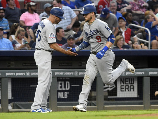 Los Angeles Dodgers' Yasmani Grandal (9) is congratulated for his home run by third base coach Chris Woodward while running bases during the third inning of a baseball game against the Atlanta Braves, Friday, July 27, 2018, in Atlanta. (AP Photo/John Amis)