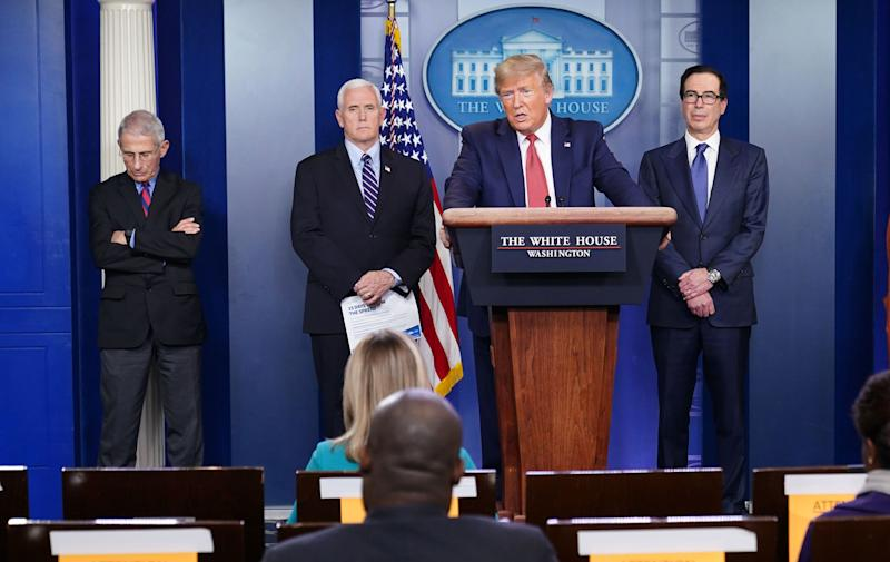 US President Donald Trump, flanked by (from R) US Treasury Secretary Steven Mnuchin, US Vice President Mike Pence and Director of the National Institute of Allergy and Infectious Diseases Anthony Fauci, speaks during the daily briefing on the novel coronavirus, COVID-19, in the Brady Briefing Room at the White House on March 25, 2020, in Washington, DC. (Photo by MANDEL NGAN / AFP) (Photo by MANDEL NGAN/AFP via Getty Images)
