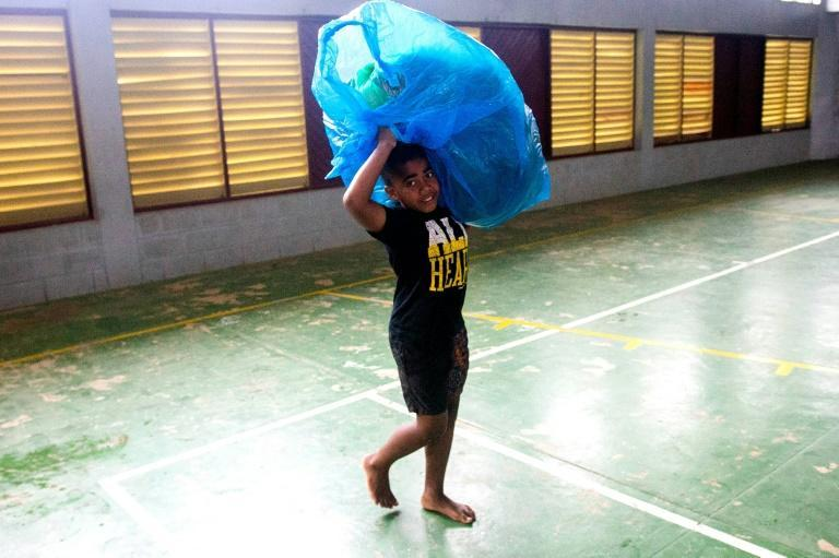 A Fijian boy carries a bag to a temporary shelter to avoid strong damaging winds from super cyclone Yasa in the capital city of Suva on December 17, 2020