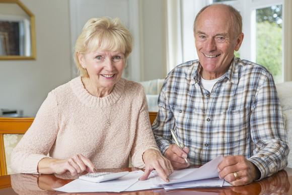 A smiling elderly couple reviewing their finances.