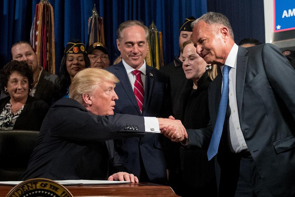 """President Donald Trump, left, accompanied by Veterans Affairs Secretary David Shulkin, center, shakes hands with Isaac """"Ike"""" Perlmutter, an Israeli-American billionaire, and the CEO of Marvel, right. (AP Photo/Andrew Harnik)"""