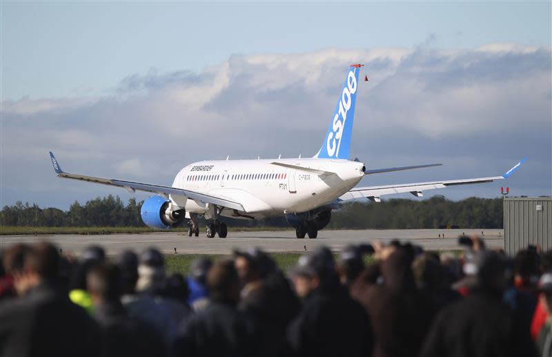 Bombardier employees and guests watch the CSeries aircraft taxi on the runway for its first test flight in Mirabel, Quebec