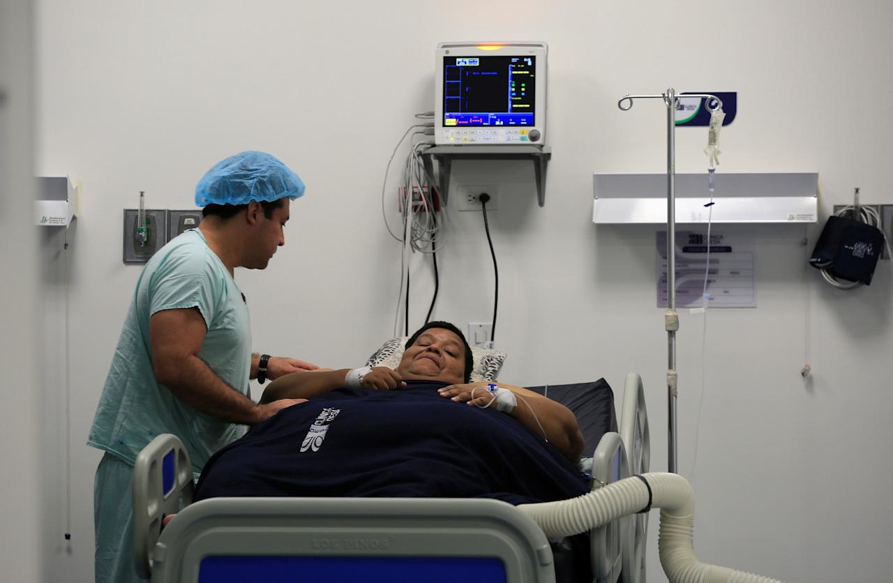 Oscar Vasquez Morales, 44, considered the most obese man in the country at about 400 kg, gestures next to bariatric surgeon in clinic in Cali, Colombia, May 16, 2016.