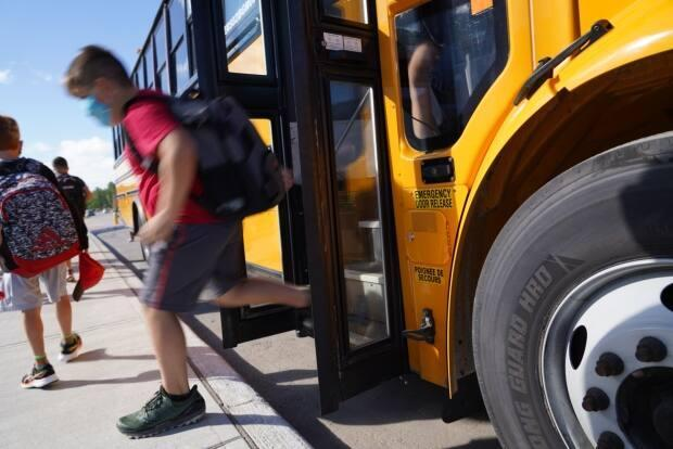 A student descends from a school bus in Ottawa last August. On Friday, the city's medical officer of health warned that it's likely schools will stay shut after spring break due to rising COVID-19 cases. (Francis Ferland/CBC - image credit)