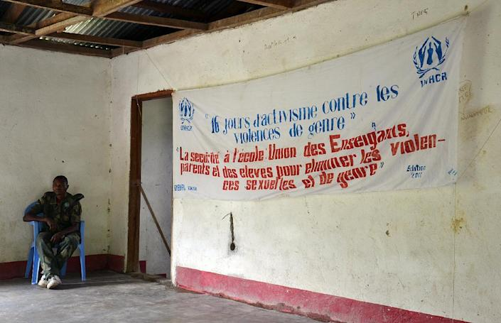 """A soldier sits next to a banner reading 'Sixteen days of actions against sexual violences"""" during a campaign against sexual violence led by the UNHCR at the cultural center of Buburu, northwestern DR Congo (AFP Photo/Habibou Bangre)"""