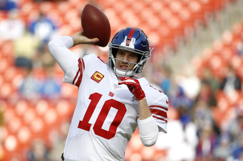 FILE - In this Dec. 22, 2019 file photo New York Giants quarterback Eli Manning works out prior to an NFL football game against the Washington Redskins in Landover, Md. Manning, who led the Giants to two Super Bowls in a 16-year career that saw him set almost every team passing record, has retired. The Giants said Wednesday, Jan. 22, 2020 that Manning would formally announce his retirement on Friday. (AP Photo/Patrick Semansky, file)