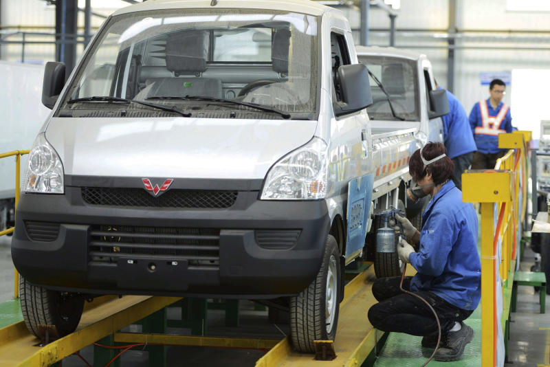In this photo taken Wednesday April 16, 2014, workers put the finishing touch to a pickup at a factory of SGMW, a joint venture between Chinese carmakers and General Motors in Qingdao in east China's Shandong province. China's automakers are the underdogs heading into next week's Beijing auto show, where foreign and domestic brands will jostle for attention in a crowded market. Facing intense competition from General Motors, Volkswagen and other global rivals, local brands such as Chery, Geely and SUV maker Great Wall have seen sales and market share shrink this year while China's overall market grew. (AP Photo) CHINA OUT