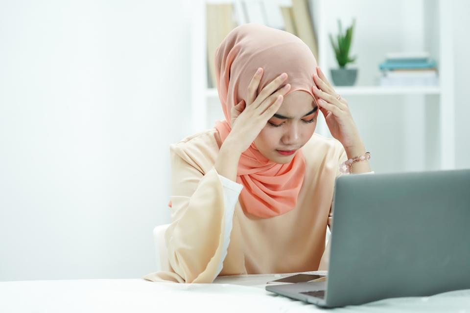 Stressed Muslim businesswoman feeling sick and tired while working a in office. girl is feeling headache when working.