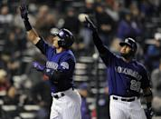 Colorado Rockies Troy Tulowitzki, left, and Wilin Rosario, right, celebrate a home run by Tulowitzki in the sixth inning of the MLB baseball game against the Chicago White Sox on Monday, April 7, 2014, in Denver. The Rockies won 8-1. (AP Photo/Chris Schneider)