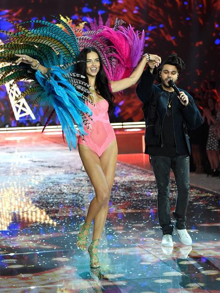 "<p>Kicking off the ""Exotic Butterflies"" part of the show, Adriana Lima slinked out in a hot pink bodysuit and ROYGBV feather wings to The Weeknd's soulful voice. </p>"