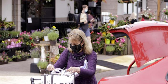 A woman wearing a purple top wearing a mask inspects her grocery shopping standing by an open trunk of a red car.