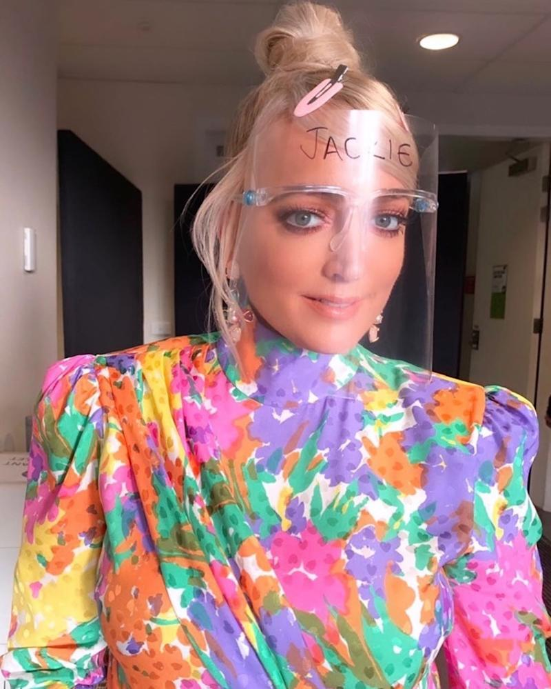 Jackie 'O' Henderson wearing a plastic face shield and a colourful dress backstage on The Masked Singer