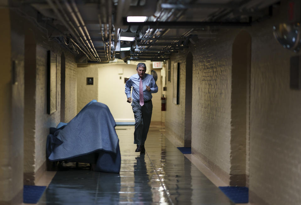 FILE - In this June 16, 2021, file photo Sen. Joe Manchin, D-W.Va., one of the key Senate infrastructure negotiators, rushes back to a basement room at the Capitol as he and other Democrats work behind closed doors, in Washington. Congress is hunkered down, grinding through an eight-week stretch as the president's Democratic allies in the House and Senate try to shape his big infrastructure ideas into bills that could actually be signed into law. Perhaps not since the drafting of Obamacare more than a decade ago has Washington tried a legislative lift as heavy as this. (AP Photo/J. Scott Applewhite, File)