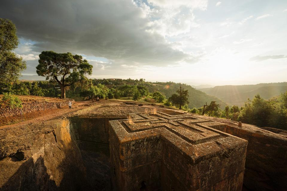 """In northern <a href=""""https://www.cntraveler.com/story/go-to-ethiopia-for-ancient-history-jazz-and-a-capital-city-on-the-rise?mbid=synd_yahoo_rss"""" rel=""""nofollow noopener"""" target=""""_blank"""" data-ylk=""""slk:Ethiopia"""" class=""""link rapid-noclick-resp"""">Ethiopia</a>, the small town of <a href=""""https://www.cntraveler.com/gallery/the-sacred-rock-churches-of-lalibela-ethiopia?mbid=synd_yahoo_rss"""" rel=""""nofollow noopener"""" target=""""_blank"""" data-ylk=""""slk:Lalibela"""" class=""""link rapid-noclick-resp"""">Lalibela</a> is known for its eleven medieval churches carved out of monolithic rock. Dating back to the twelfth century, the churches were built on orders of King Lalibela, who envisioned the creation of a """"New Jerusalem"""" during a time when pilgrimages to the holy land were hindered by Muslim conquests. Today the site still sees many pilgrimages, largely from Coptic Christians. The structures, complete with catacombs and ceremonial passages, are fascinating; the Church of St. George, or Biete Ghiorgis (pictured), is particularly famous for its cross-shaped design and network of trenches, which connects it to the other churches."""