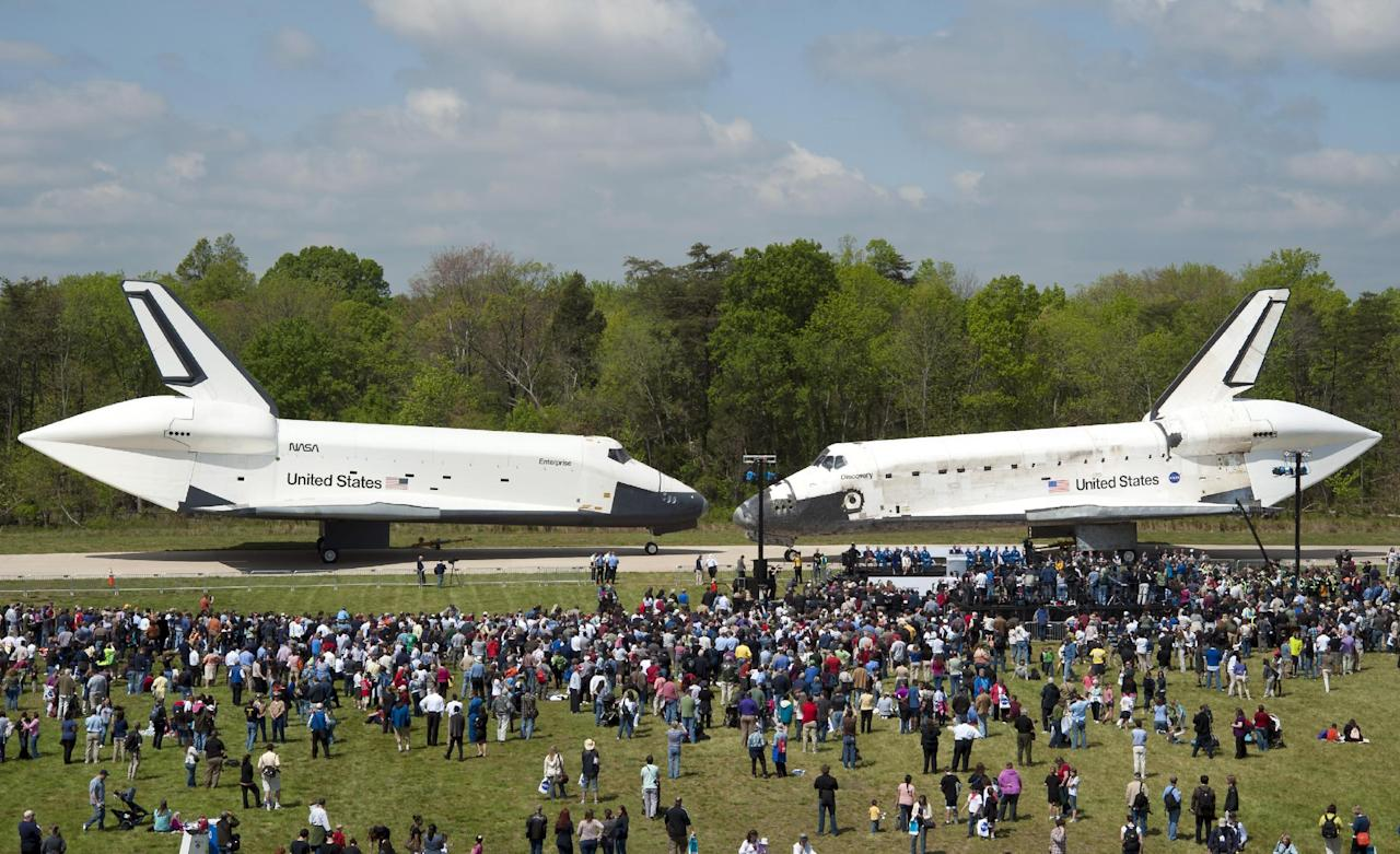 In this photo provided by the Smithsonian Institution via NASA, space shuttles Enterprise, left, and Discovery meet nose-to-nose at the beginning of a transfer ceremony at the Smithsonian's Steven F. Udvar-Hazy Center, Thursday, April 19, 2012, in Chantilly, Va. Space shuttle Discovery will take the place of Enterprise at the center to commemorate past achievements in space and retire as an artifact representing the 30-year shuttle program. (AP Photo/Smithsonian Institution via NASA, Carolyn Russo) MANDATORY CREDIT