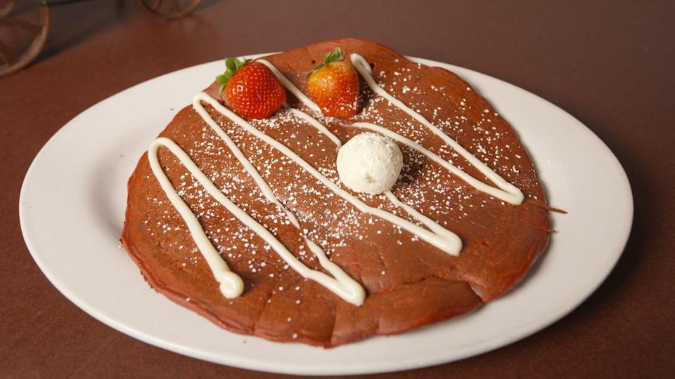 """<p>This <a rel=""""nofollow noopener"""" href=""""https://www.delish.com/restaurants/a19425404/best-breakfast-las-vegas-giant-pancakes-video/"""" target=""""_blank"""" data-ylk=""""slk:foot-wide pancake"""" class=""""link rapid-noclick-resp"""">foot-wide pancake</a> is the size of a steering wheel, and chefs have to flip it with a cement scraper. But this size isn't all the pancake's got going for it: The thing is decadently sweet-red velvet with cream cheese frosting and strawberries on top.</p>"""