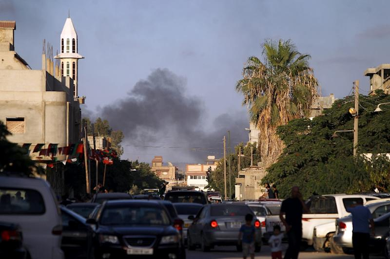 Smoke billows during clashes between security forces and armed groups near a Libyan army special forces barracks, on July 23, 2014, in the eastern city of Benghazi