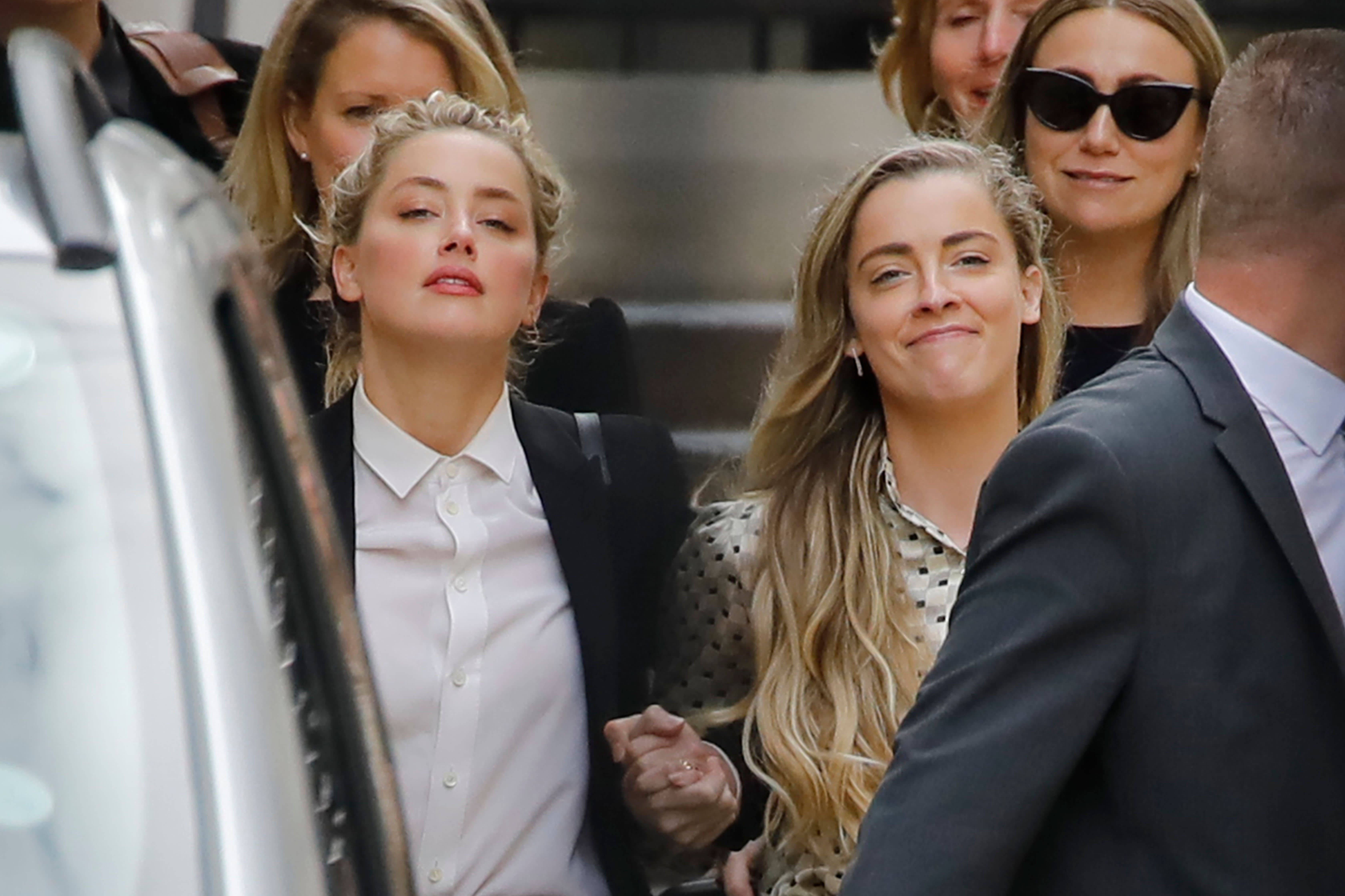 """TOPSHOT - US actress Amber Heard (L) leaves hand-in-hand with her sister Whitney Heard (R) from the High Court after a hearing in the libel trial by her former husband US actor Johnny Depp against News Group Newspapers (NGN) in London, on July 24, 2020. - Depp is suing the publishers of The Sun and the author of the article for the claims that called him a """"wife-beater"""" in April 2018. (Photo by Tolga AKMEN / AFP) (Photo by TOLGA AKMEN/AFP via Getty Images)"""