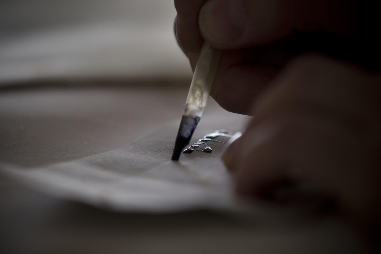 """In this Tuesday, Jan. 17 2012 photo, calligraphy expert Avraham Borshevsky practices at his studio in Jerusalem. Parchment, feathers and """"qalams,"""" a pen made of dried bamboo, are still used by sophers Jewish scribes and khattats Muslim calligraphers. (AP Photo/Bernat Armangue)"""