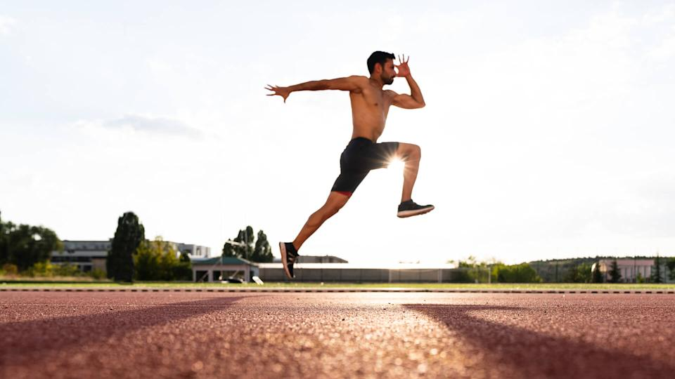 young man exercise jogging and running on athletic track on stadium at sunrise.