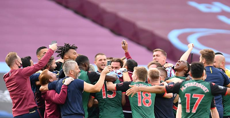 Aston Villa players and staff celebrate after all the games finished confirming their Premier League survival during the English Premier League football match between West Ham United and Aston Villa at The London Stadium, in east London on July 26, 2020. (Photo by Justin Setterfield / POOL / AFP) / RESTRICTED TO EDITORIAL USE. No use with unauthorized audio, video, data, fixture lists, club/league logos or 'live' services. Online in-match use limited to 120 images. An additional 40 images may be used in extra time. No video emulation. Social media in-match use limited to 120 images. An additional 40 images may be used in extra time. No use in betting publications, games or single club/league/player publications. / (Photo by JUSTIN SETTERFIELD/POOL/AFP via Getty Images)