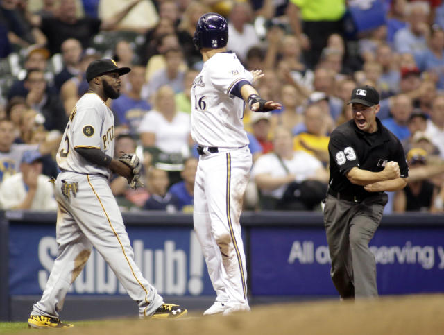 Milwaukee Brewers' Aramis Ramirez, center, is called out at third base by umpire Will Little, right, after being tagged out by Pittsburgh Pirates third baseman Josh Harrison, left, during the sixth inning of a baseball game Friday, Aug. 22, 2014, in Milwaukee. (AP Photo/Darren Hauck)