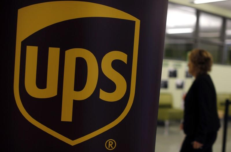 FILE PHOTO: Woman walks past a sign bearing the UPS logo at a job fair in Chicago