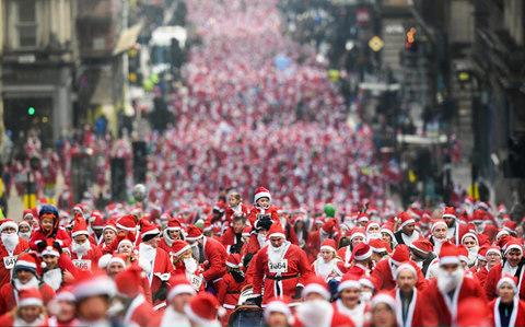 More than 8,000 members of the public take part in Glasgow's annual Santa dash on St Vincent Street - Credit: Getty