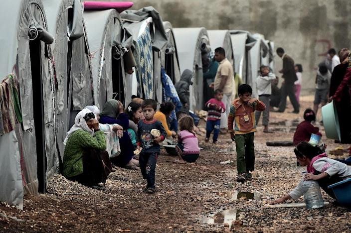 Children walk past tents at a Syrian Kurdish refugee camp in the Turkish town of Suruc on October 11, 2014 after fleeing Kobane amid an assault by Islamic State jihadists (AFP Photo/Aris Messinis)