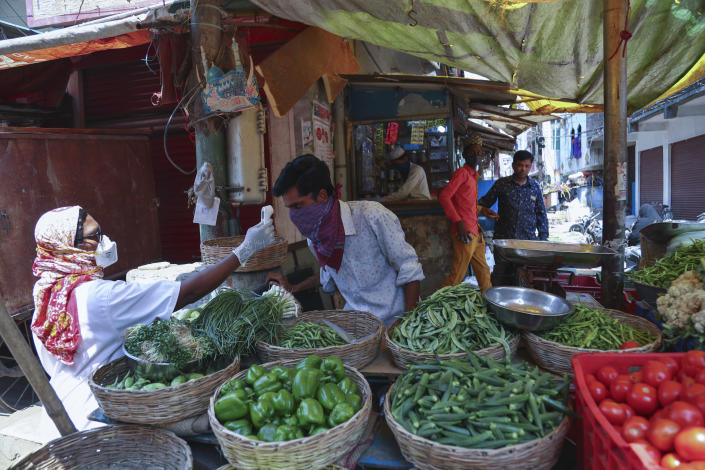 An Indian health worker checks body temperature of a vegetable vendor during a door-to-door survey being conducted as a precaution against COVID-19 in Hyderabad, India, Thursday, May 6, 2021. (AP Photo/Mahesh Kumar A.)
