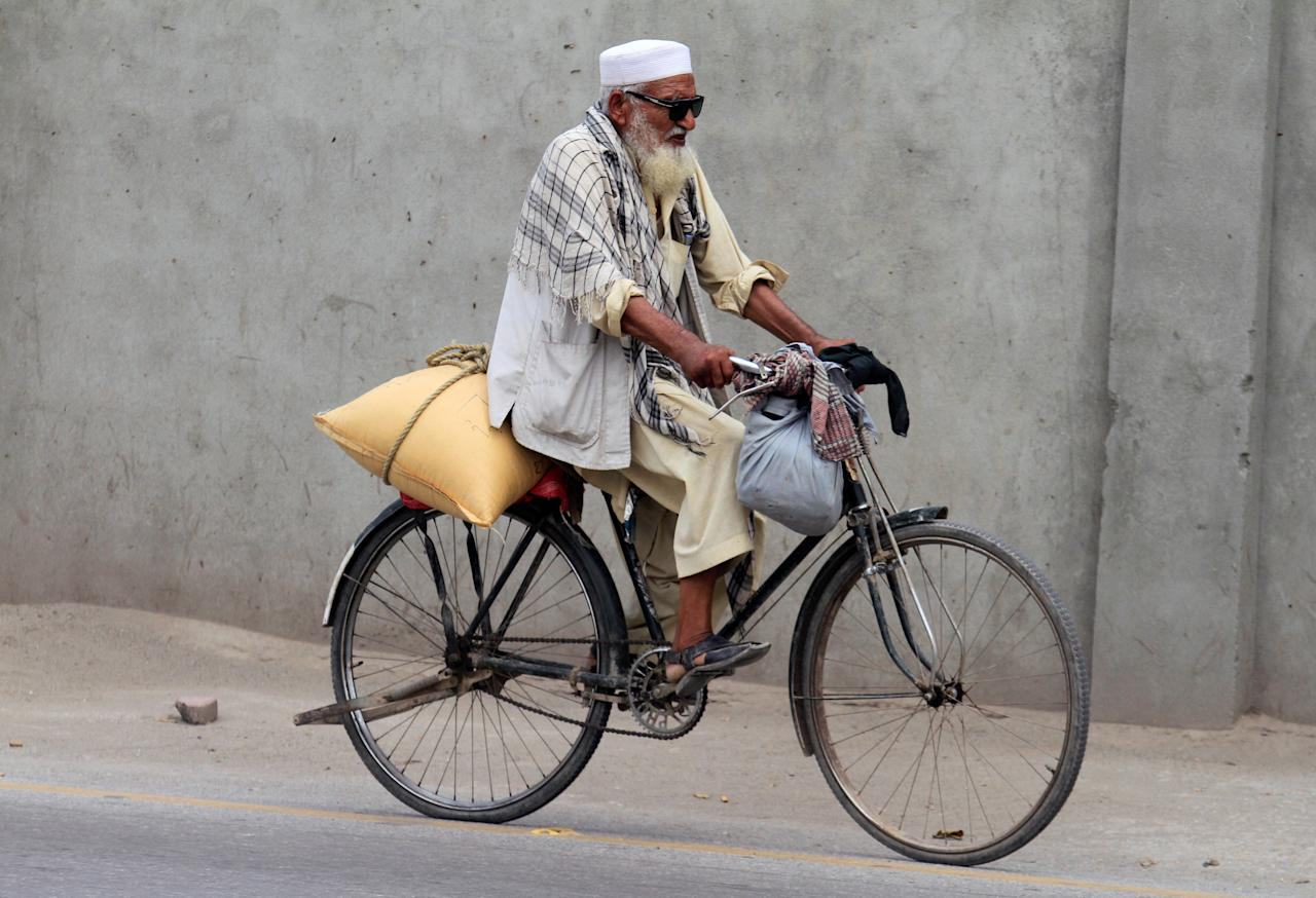 A senior man rides his bicycle on a street in Peshawar, Pakistan, June 28, 2017.  REUTERS/Fayaz Aziz