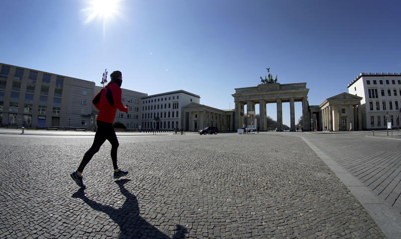 A man jogs on the square in front of the Brandenburg Gate in Berlin, Germany, Tuesday, March 24, 2020. In order to slow down the spread of the coronavirus, the German government has considerably restricted public life and asked the citizens to stay at home and keep distance from other people. (AP Photo/Michael Sohn)