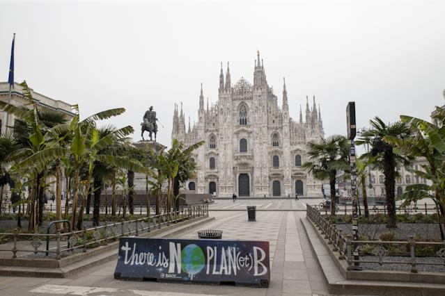 """An environmental protest banner, reading """"there is no plan(et) B"""" sits on the edge of an empty Duomo square in view of Duomo Cathedral, in Milan, Italy, on March 10, 2020. (Credit: Camilla Cerea/Bloomberg)"""
