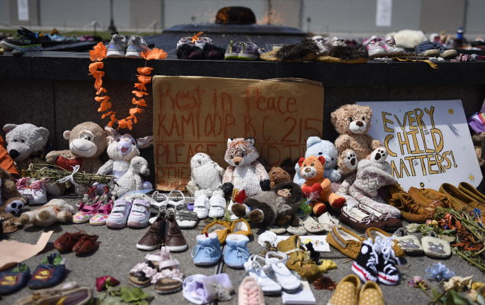 Shoes, stuffed animals, flowers and signs are left against the Centennial Flame at a memorial for the 215 children whose remains were found at the grounds of the former Kamloops Indian Residential School at Tk'emlups te Secwépemc First Nation in Kamloops, B.C., on Parliament Hill in Ottawa on Friday, June 4, 2021. (Justin Tang/The Canadian Press via AP)