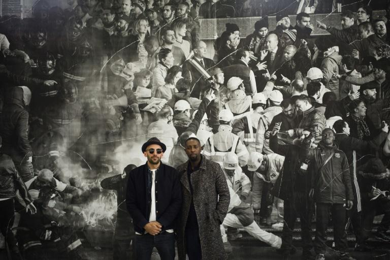 JR and Ladj Ly pose in front of a fresco of the inhabitants of the Clichy-Montfermeil