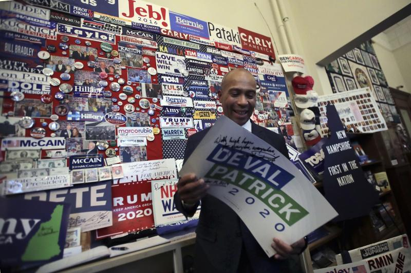 Former Massachusetts Gov. Deval Patrick adds his campaign sign to pins, signs and bumper stickers of New Hampshire primary presidential contenders on display in the State House visitors' center on Nov. 14 in Concord, N.H. (Photo: Charles Krupa/AP)