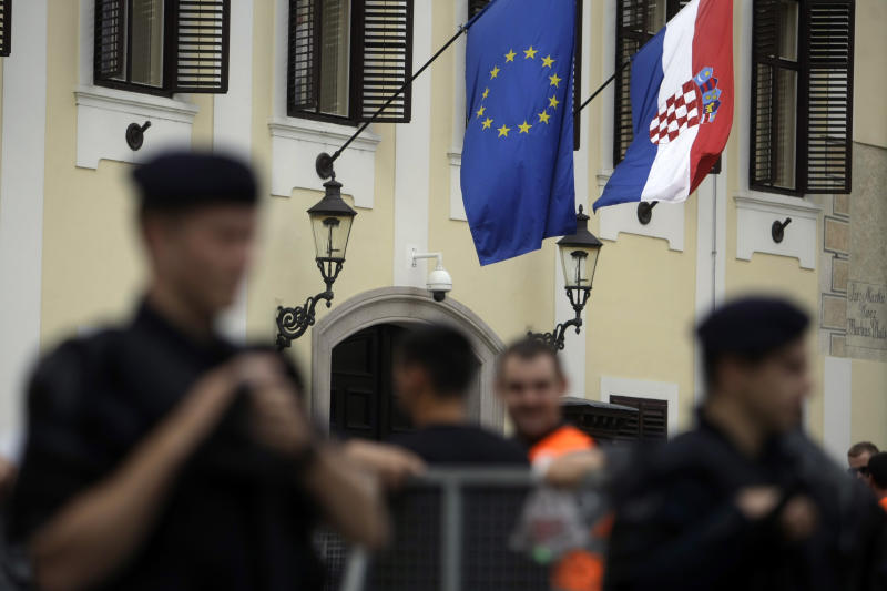 In this photo taken Thursday, June 6, 2013, police officers stand in front of a building adorned with EU and Croatian flags in Zagreb, Croatia. A decade back when Croatia started negotiating the EU entry, then the war torn country was overjoyed at the prospect of becoming a member of European elite. With the EU in deep financial turmoil and Croatia's own economy in recession for five consecutive years, the excitement has dimmed as the Balkan country gets ready to officially become the 28th EU member on July 1. (AP Photo/ Marko Drobnjakovic)
