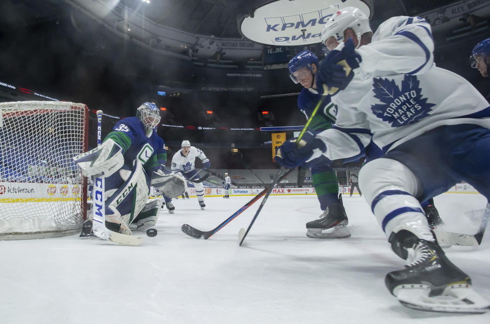 Vancouver Canucks goalie Thatcher Demko (35) makes the save as Tyler Myers, back right, checks Toronto Maple Leafs' Travis Boyd during the second period of an NHL hockey game in Vancouver, British Columbia, on Saturday, March 6, 2021. (Darryl Dyck/The Canadian Press via AP)