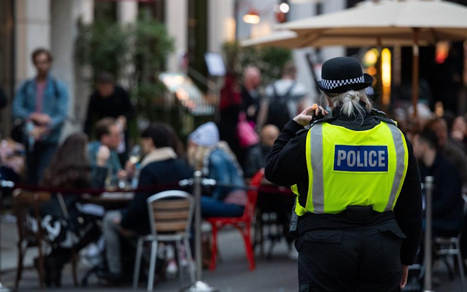Police monitor people seated outside bars and restaurants in Soho, London, on the first day after the city was put into Tier 2 restrictions to curb the spread of coronavirus - Dominic Lipinski/PA Wire