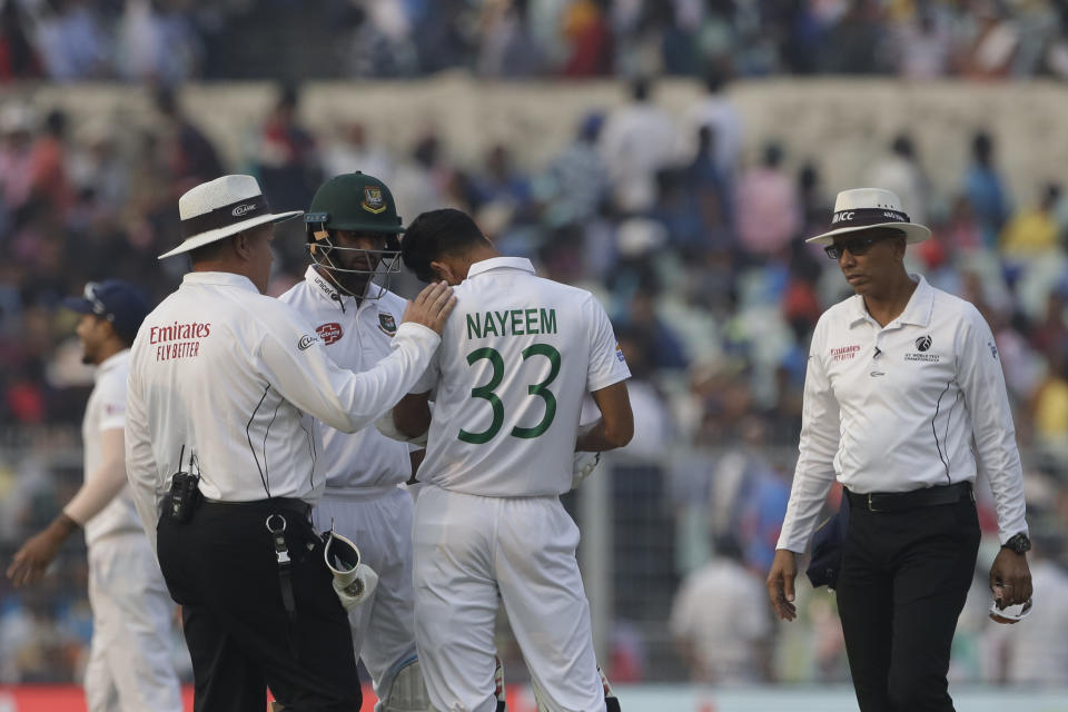 Umpire Marais Erasmus, left, talks to Bangladesh's Nayeem Hasan after he was injured by a delivery from India's Mohammed Shami during the first day of the second test match between India and Bangladesh, in Kolkata, India, Friday, Nov. 22, 2019. (AP Photo/Bikas Das)