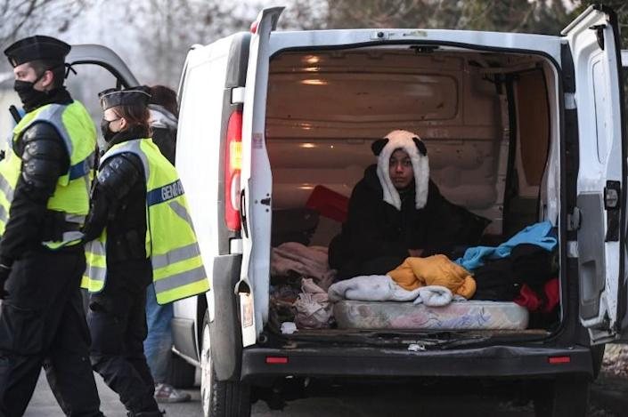 A raver wearing a panda hat sits in a van after being questioned by French police following the breakup of the event