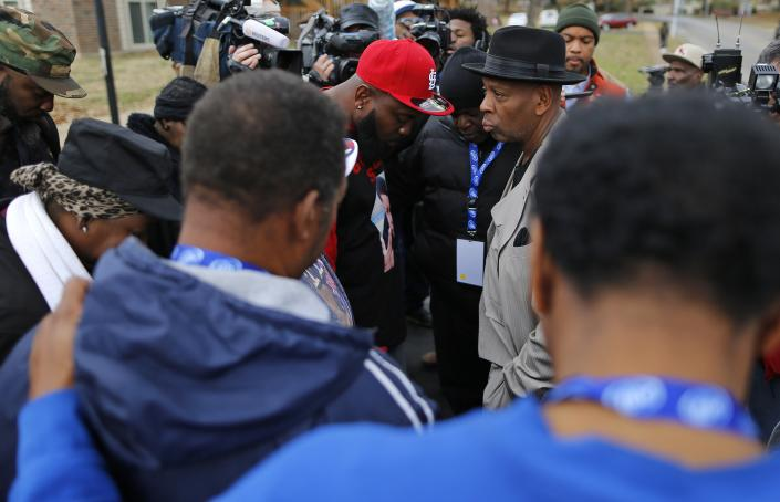 Michael Brown Sr. (red hat) prays with others Saturday near where his son was killed in Ferguson, Mo. 106 days ago. (Reuters/Jim Young)
