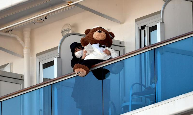 A passenger on the Diamond Princess shows off a teddy bear from her balcony