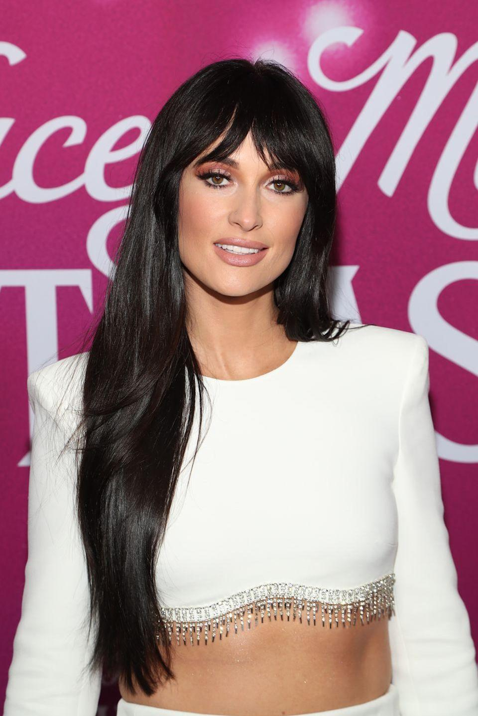 """<p>A fresh set of curtain bangs can add an easy touch of retro-style glam, especially if you have <a href=""""https://www.goodhousekeeping.com/beauty/hair/a34377/how-to-grow-hair-faster-tips/"""" rel=""""nofollow noopener"""" target=""""_blank"""" data-ylk=""""slk:long, sleek hair"""" class=""""link rapid-noclick-resp"""">long, sleek hair</a> like Kacey Musgraves.</p>"""