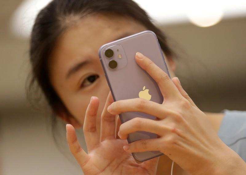 FILE PHOTO: A customer tests Apple's iPhone 11 after it went on sale at the Apple Store in Beijing