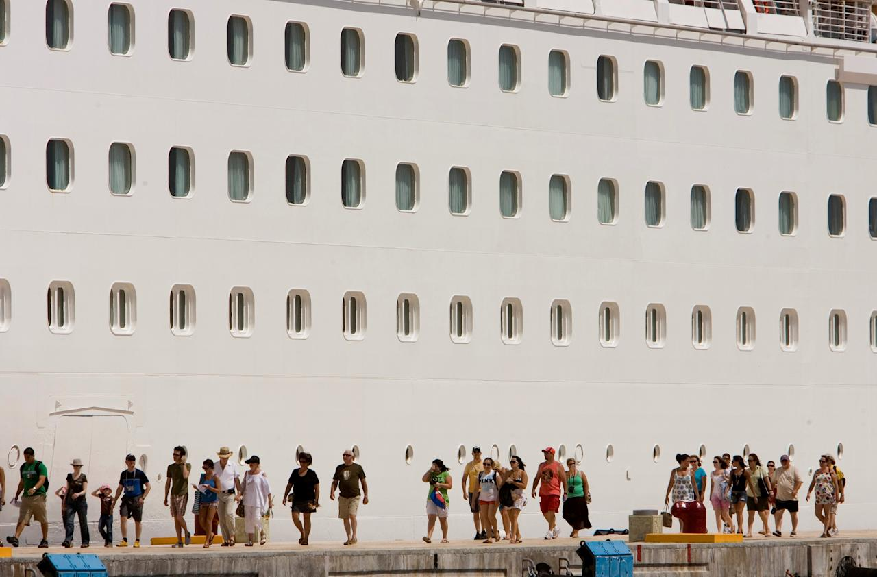 FILE PHOTO: Tourists walk beside Royal Caribbean's cruise ship 'Enchantment of the Seas' after they arrive in Cozumel, Mexico May 27, 2009.   REUTERS/Gerardo Garcia/File Photo                               GLOBAL BUSINESS WEEK AHEAD.   SEARCH GLOBAL BUSINESS 22 JAN FOR ALL IMAGES