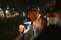 Police officers blow out candles lit by people marking the anniversary of the military crackdown on a pro-democracy student movement in Beijing, outside Victoria Park in Hong Kong, Friday, June 4, 2021. A member of the committee that organizes Hong Kong's annual candlelight vigil for the victims of the Tiananmen Square crackdown was arrested early Friday on the 32nd anniversary. (AP Photo/Kin Cheung)