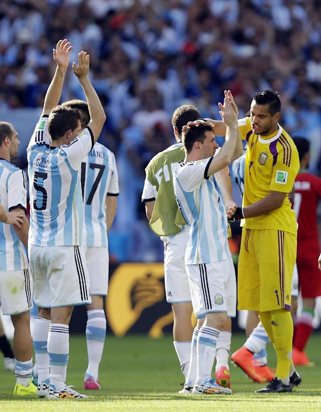 Argentina's goalkeeper Sergio Romero pats Lionel Messi, second right, after their 1-0 victory over Iran during the group F World Cup soccer match between Argentina and Iran at the Mineirao Stadium in Belo Horizonte, Brazil, Saturday, June 21, 2014. (AP Photo/Fernando Vergara)