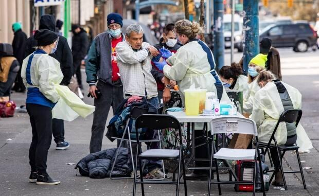 A nurse administers a COVID-19 vaccination to at-risk people in the Downtown Eastside neighbourhood of Vancouver on Tuesday.