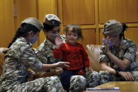 """Members of the Lebanese General Security forces play with an Albanian child during an operation to take them back home to Albania from al-Hol, northern Syria, at the Rafik Hariri International Airport in Beirut, Lebanon, Tuesday, Oct. 27, 2020. The repatriation of four children and a woman related to Albanian nationals who joined Islamic extremist groups in Syria """"is a great step"""" to be followed by more repatriations, Albania's prime minister said Tuesday. (AP Photo/Bilal Hussein)"""